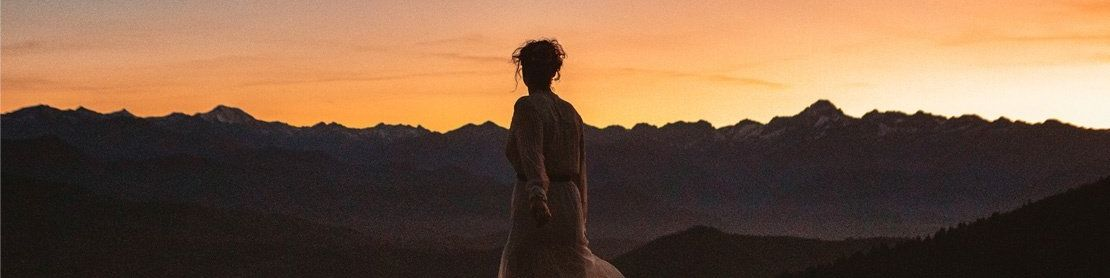 A woman stands with her back to the camera, watching an orange sunset over dark mountains. She wears a pale dress, and her hair is worn up, with tendrils outlined in shadow.